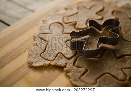 Gingerbread man mould on dough over cutting board