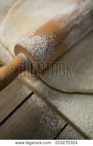Close up of rolling pin on rolled dough over cutting board at table