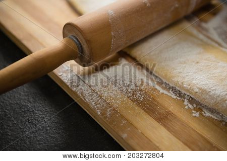 Cropped image of wooden rolling pin on dough over cutting board at table