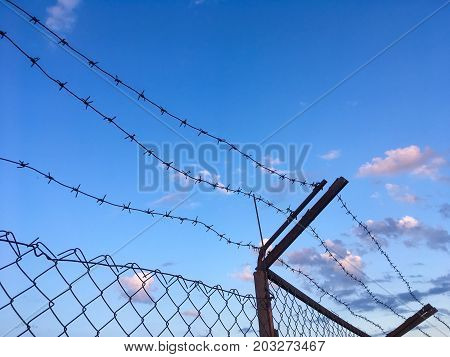 Barbed wire on top of an iron fence against a blue sky, imprisonment concept