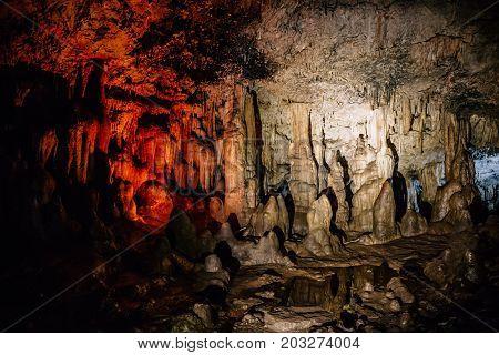 Stalactites and stalagmites inside cave, speleology concept