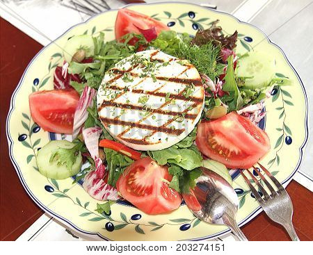 Salad of tomato arugula olives cucumbers pepper and toasted cheese. Greek cuisine