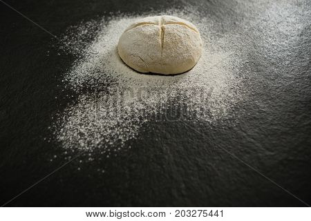 High angle view of flour on unbaked bun on table