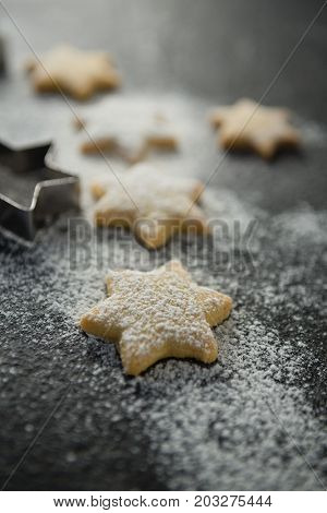 Close up of flour on star shape unbaked cookies at table