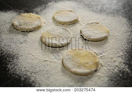 Flour on unbaked cookies on table