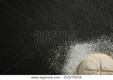 Cropped image of flour on unbaked bun at table