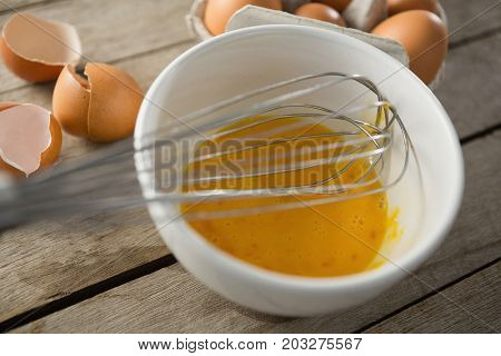Close up of egg in bowl with wire whisk by eggshells on wooden table