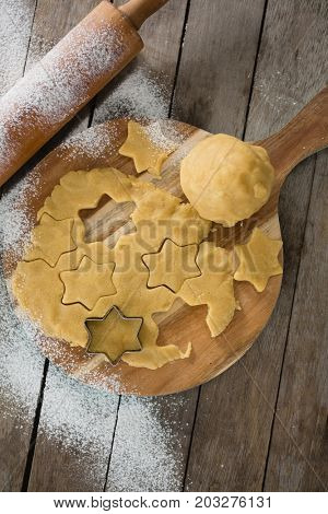 Overhead view of dough on cutting board with star shape cutter and rolling pin at table