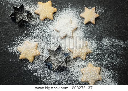 Overhead view of star shape cookies with pastry cutter on gray table