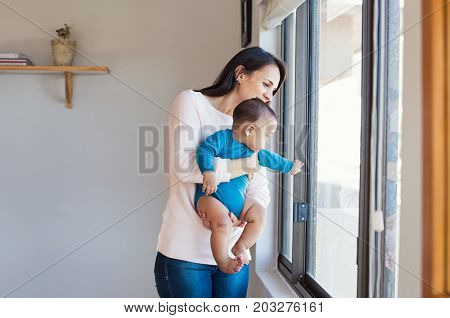 Latin mother holding her baby and looking out of window. Happy new mom hugging her toddler boy at home. Hispanic woman holding newborn boy near the window and awaiting dadâ??s arrival.