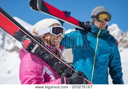 Happy couple on ski holiday in snowy mountains. Smiling young couple with ski on shoulder standing on mountain covered by snow. Happy woman with ski board looking away with her boyfriend.