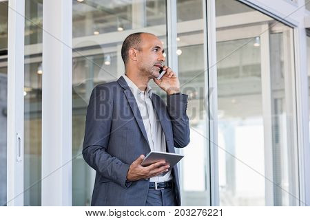 Mature leader talking on phone and looking away. Senior business man in formal have a serious conversation at cellphone. Businessman discussing over phone during working call.