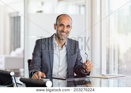 Happy mature business man holding spectacles in modern office. Successful senior businessman sitting in meeting room with phone and tablet. Smiling man in suit at elegant office.
