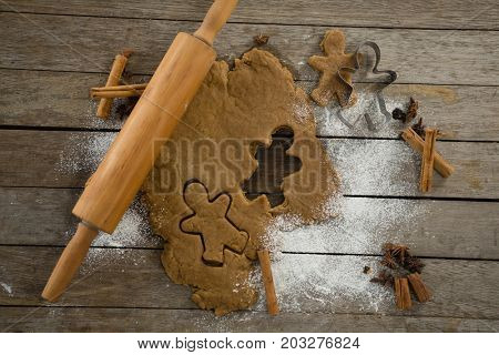 Overhead view of dough with pastry cutter and rolling pin on wooden table
