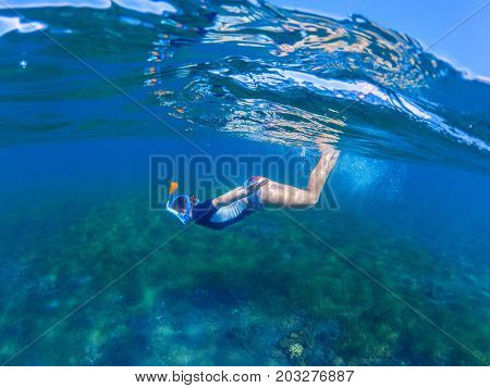 Snorkeling woman dives to sea bottom. Snorkeling girl in full-face snorkeling mask. Sea wild life. Snorkel undersea. Seashore underwater photo. Active seaside vacation. Water sport in tropical sea