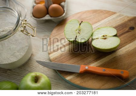 High angle view of granny smith apple halved on cutting board by egg carton on table