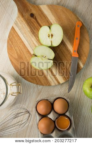 Overhead view of granny smith apple halved on cutting board by egg carton on table