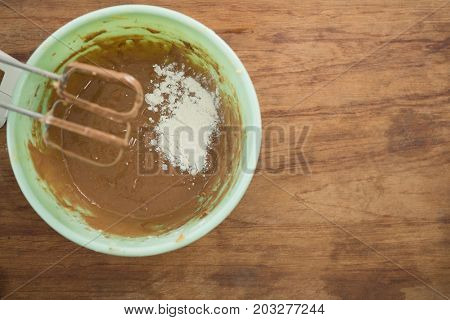Overhead view of flour with chocolate batter in bowl by electric mixer on wooden table