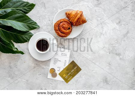 Pay restaurant bill. Bill, bank card, coins near cup of coffee and baking on light table top view.