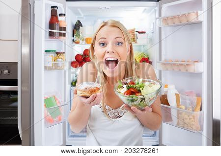 Close-up Of Young Woman Holding Bowl Of Salad And Bun Standing In Front Of Fridge