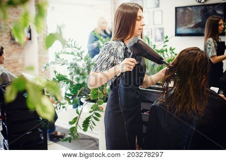 Master hairdresser dries hair with a hairdryer to client keratin t girl. concept of hair care, healthy hair, straight hair.