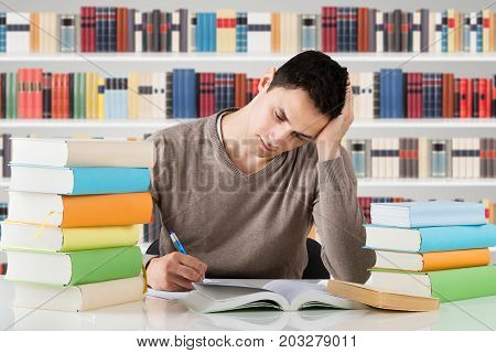 Stressful University Student Studying In Front Of Bookshelf At Library