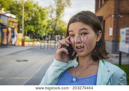 Bad news. Girl teenager talking on the phone outdoors