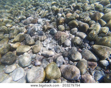 Seashore pebbles underwater photo texture. Seaside beach with smooth stones. Marine pebbles undersea texture. Beach stones background. Pebbles in seawater under sunlight. Tropical island shore