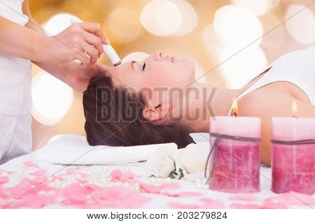 Close-up Of A Relaxed Young Woman Undergoing Microdermabrasion Therapy On Forehead