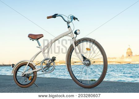 Vintage bike against riverside cityscape. Neva river quay Saint Petersburg Russia