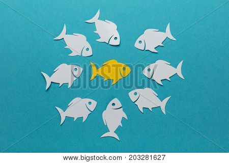 Yellow Fish Surrounded By White Paper Fishes Over Blue Background