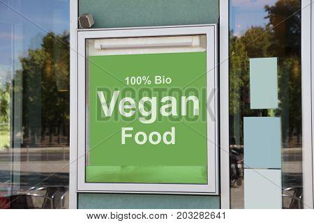 Closeup of vegan food sign outside modern restaurant building