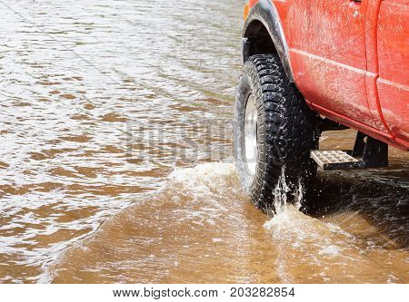 A 4wd truck running through a flooded road