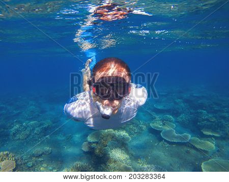 Young man underwater portrait. Male snorkel in tropical lagoon undersea photo. Snorkeling in coral reef. Tropical sea activity. Water sport. Exploring tropical coral reef. Man in snorkeling mask