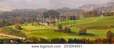 Panoramic View Of Beautiful Mountain Rural Landscape In Alps With Village In Background
