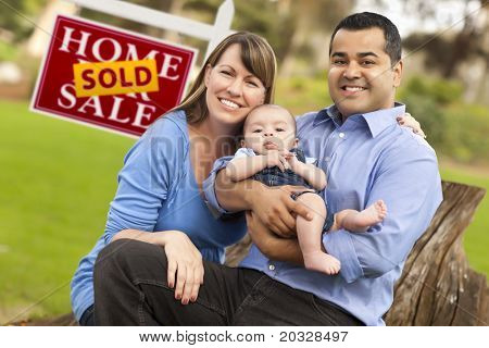 Happy Mixed Race Couple with Baby in Front of Sold Real Estate Sign.