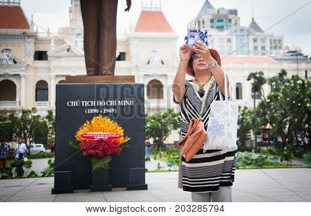 HO CHI MINH CITY (SAIGON), VIETNAM - JULY 2017 : Unidentified tourist taking a selfie with Ho Chi Minh statue in front of City Hall, Saigon, Ho Chi Minh City, Vietnam