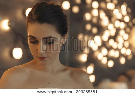 thoughtful girl in dim light. young woman in a dress with bare shoulders closeup. Copy space for your text