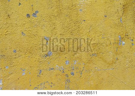 Weathered yellow painted concrete wall. Sunny rough plaster photo texture. Shabby chic backdrop. Old concrete surface with stains. Distressed texture in warm shades. Obsolete concrete wall top view