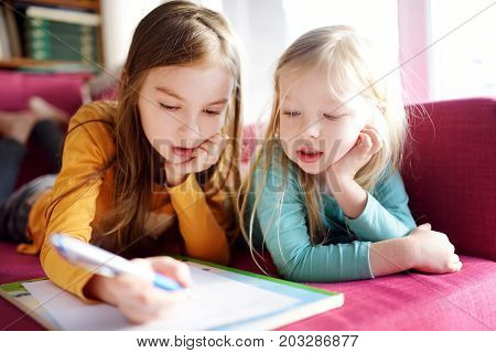 Two Cute Little Sisters Writing A Letter Together At Home. Older Sister Helping Youngster With Her H