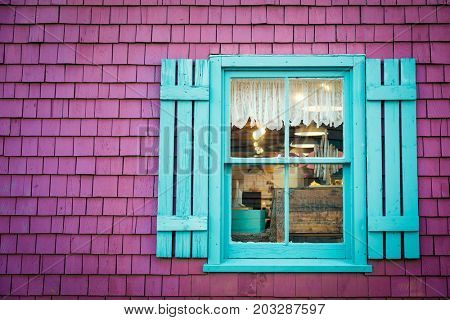 Detail of an old shuttered window on shingle wall. Traditional building exterior in Prince Edward Island, Canada. Space for text.