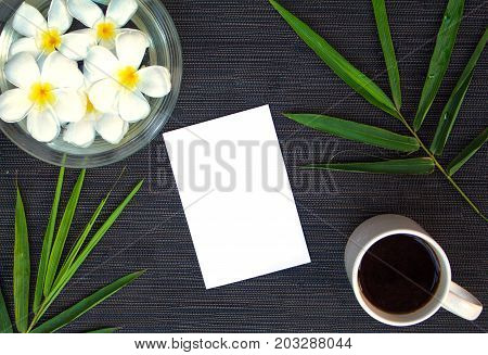 Bamboo leaf and frangipani flower on rustic wooden background. Blank card and floral decor top view. White paper in plumeria and bamboo. Exotic vacation travel. Spa or beauty banner with text place