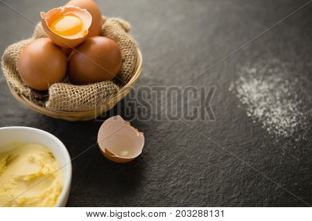 Close up of butter and eggs in bowls on table