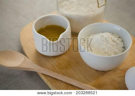Flour and oil in containers on cutting board at table