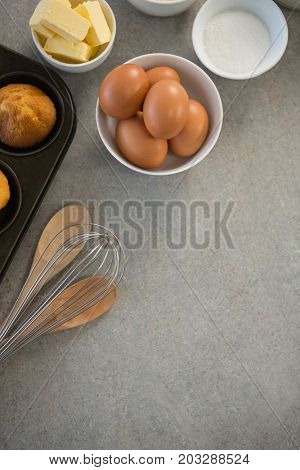 Overhead view of ingredients by muffin tin on table
