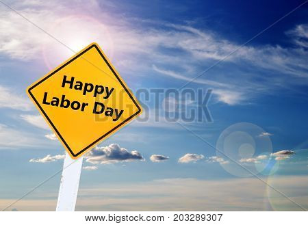 Labor Day is a federal holiday of United States America. Text for Happy Labor Day on yellow road sign with blurred blue sky and cloud background with sunlight. Space for any design