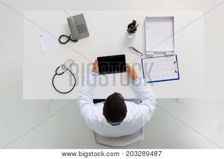 medicine, healthcare, cardiology and people concept - doctor with tablet pc computer and cardiogram sitting at table in clinic
