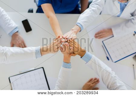 medicine, healthcare and teamwork concept - group of doctors with cardiograms making high five at hospital