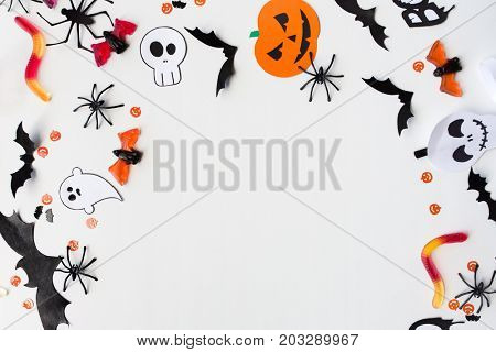 holidays, decoration and party concept - halloween paper decorations and sweets with blank copy space over white background