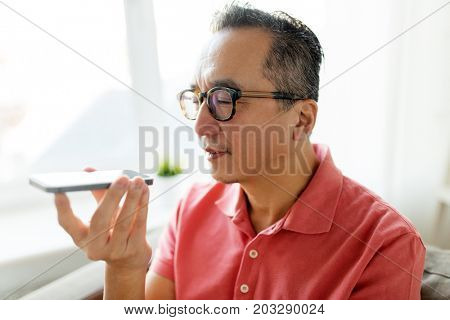 technology, lifestyle and communication concept - happy man using voice command recorder on smartphone at home